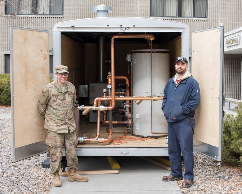 Staff Sergeant Zachary Sustar, 366th CES/HVAC, and Chris Stenson, 366th CES/HVAC stand next to the water boiler they built to help restore heating February 7, 2019 at Mountain Home Air Force Base. the boiler was built in a trailer and designed to be portable to any building on the base. (U.S. Air Force photo by Senior Airman Tyrell Hall)