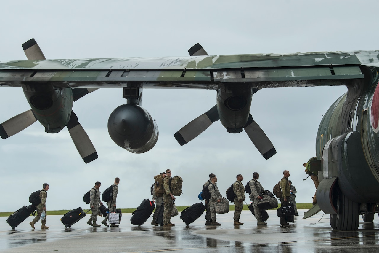 Line of troops load into cargo plane