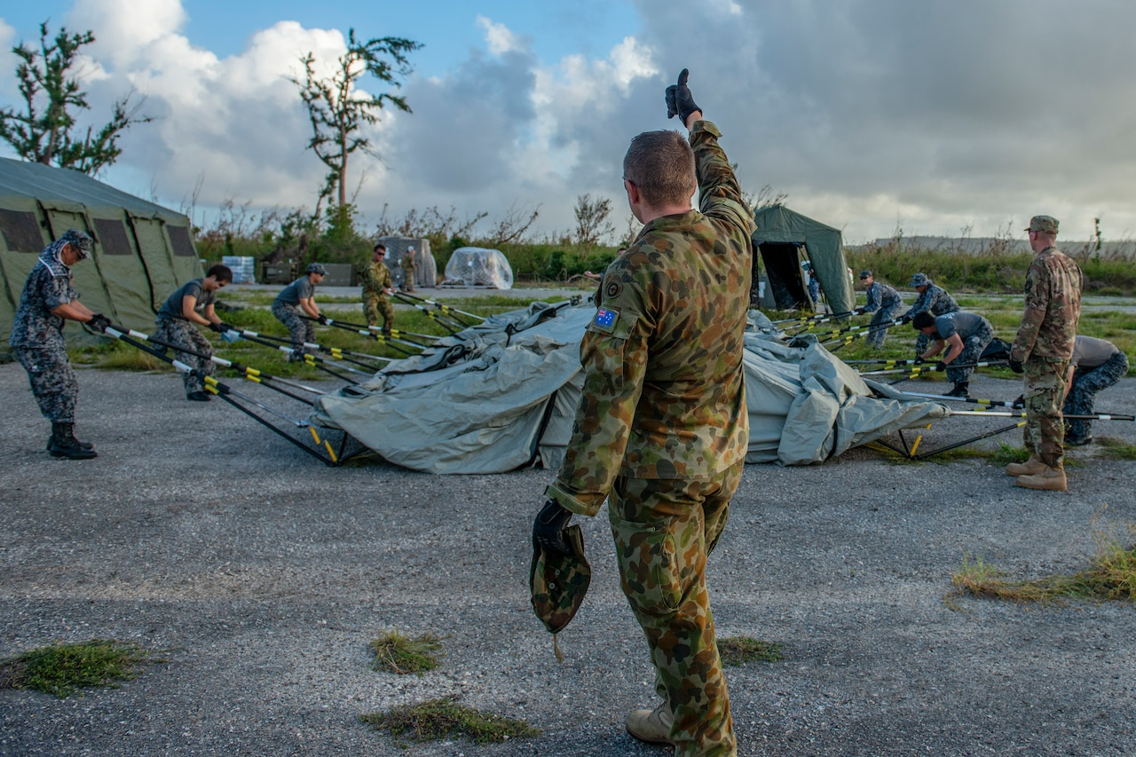 Man supervises troops setting up a tent