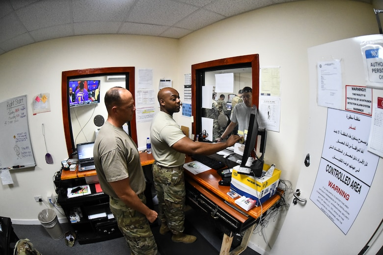 Maj. Christopher Wilkes, 380th Air Expeditionary Wing comptroller, and Staff Sgt. Ellis Robinson, 380th AEW customer service technician and cashier, assist a customer at Al Dhafra Air Base, United Arab Emirates, Mar. 7, 2019. From determining the availability of funds to processing the dispersal of payments to performing audits, the 380th AEW financial management team keeps a watchful eye on ADAB's financial data to ensure that funds are being utilized responsibly and efficiently. (U.S. Air Force photo by Senior Airman Mya M. Crosby)