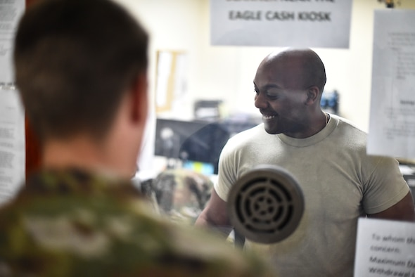 Staff Sgt. Ellis Robinson, 380th Air Expeditionary Wing customer service technician and cashier, assists a customer at Al Dhafra Air Base, United Arab Emirates, Mar. 7, 2019. Financial Management is responsible for advising, interacting and coordinating with organizations on financial matters. (U.S. Air Force photo by Senior Airman Mya M. Crosby)