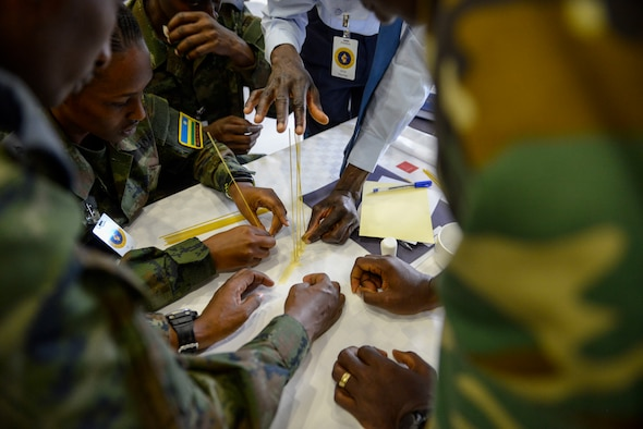 Participants in the African Partnership Flight Rwanda work together during an ice breaker - the marshmallow challenge - in Kigali, Rwanda, March 4, 2019. The challenge is designed to facilitate communication within teams and get them to look at a task from various perspectives. The African Partnership Flight program aims to build aviation capacity, enhance regional cooperation, and increase interoperability by creating opportunities for African nations to work and collaborate together. (U.S. Air Force photo by Tech. Sgt. Timothy Moore)
