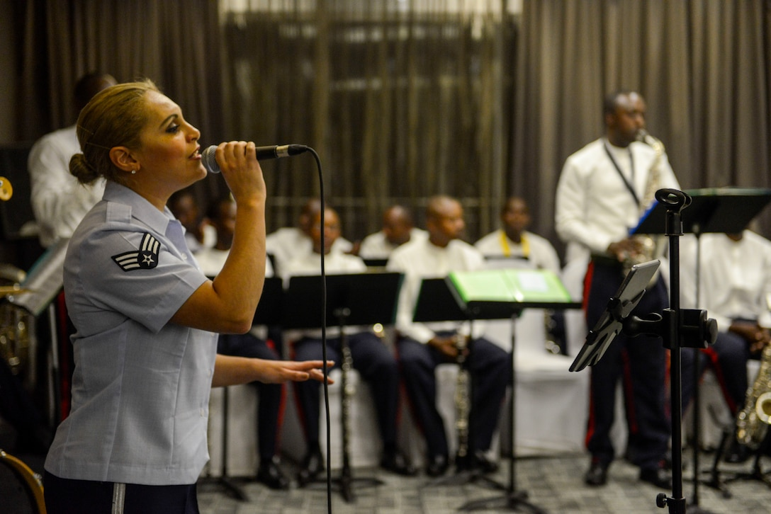 U.S. Air Force Senior Airman Linda Casul, U.S. Air Forces in Europe Band vocalist, sings a song accompanied by musicians of the Rwanda Defence Force Band during an African Partnership Flight Rwanda cultural dinner in Kigali, Rwanda, March 7, 2019. The bands used music to enhance the people-to-people relationship between the United States, Rwanda, and the other participating countries in the APF Rwanda. (U.S. Air Force photo by Tech. Sgt. Timothy Moore)