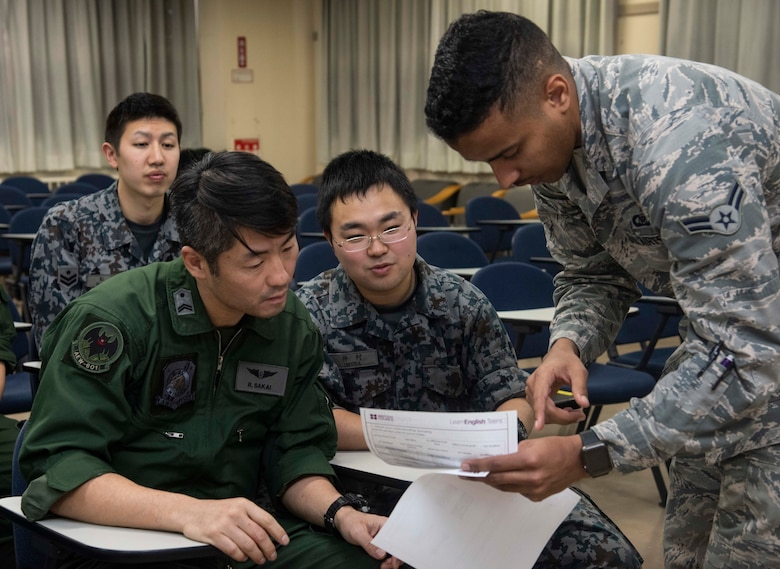 Japan Air Self-Defense Force Tech. Sgt. Ryouta Sakai, left, a 601st Squadron, Airspace Warning Control Wing operator and Airman 1st Class Taichi Imura, center, a 601st SQ AWC Wing dispatcher, receive assistance from U.S. Air Force Airman 1st Class William Raley, right, a 610th Air Control Flight weapons director technician, during an English class at Misawa Air Base, Japan, March 7, 2019. Raley said his English classes help break down language barriers between the two teams, enabling them to work more cohesively. (U.S. Air Force photo by Senior Airman Sadie Colbert)