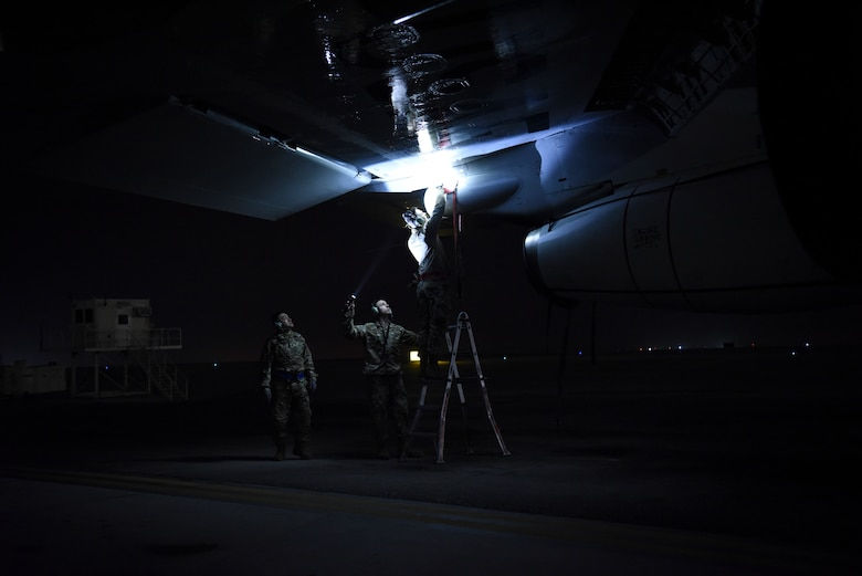 380th Expeditionary Aircraft Maintenance Squadron crew chief members inspect underneath the wing of an E-3 Sentry after landing at Al Dhafra Air Base, United Arab Emirates, Mar. 7, 2019.