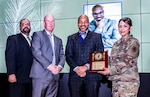 Todd Walker (center) was honored Feb. 27 as the 2019 Carter G. Woodson Community Award recipient for his outstanding contributions to the African American community. Also pictured from left to right: Defense Logistics Agency Land and Maritime Equal Employment Opportunity Office Director Charles Palmer, Defense Finance and Accounting Service-Columbus Chief of Staff Wade Brockwell and DLA Land and Maritime Chief of Staff Air Force Col. Janette Ketchum.