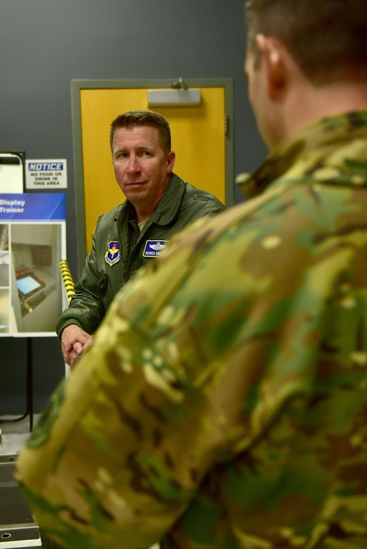 A man wearing the Air Force flight suite talks to a man wearing the operational camouflage uniform.