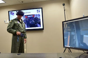A man wearing the Air Force flight suit uses virtual reality training devices.