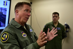 A man wearing the Air Force flight suit talks to an audience.