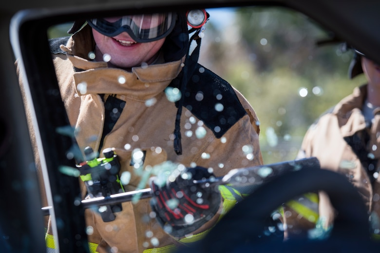 A 6th Civil Engineer Squadron firefighter breaks a car window during a joint firefighting training exercise at MacDill Air Force Base, Fla., March 6, 2019.