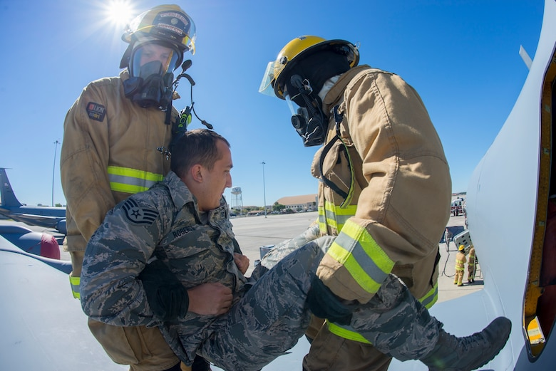 Two Wyoming Air National Guard firefighters from the 153rd Airlift Wing in Cheyenne, Wyo., extract a simulated victim from a KC-135 Stratotanker aircraft during a joint firefighting training exerc8se with firefighters from the 6th Civil Engineer Squadron at MacDill Air Force Base, Fla., March 6, 2019.