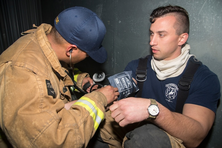 A firefighter measures the vital signs of Senior Airman Kyle Coleman, right, both assigned to the 153rd Airlift Wing in Cheyenne, Wyo., during a joint, firefighting training exercise at MacDill Air Force Base, Fla., March 5, 2019.