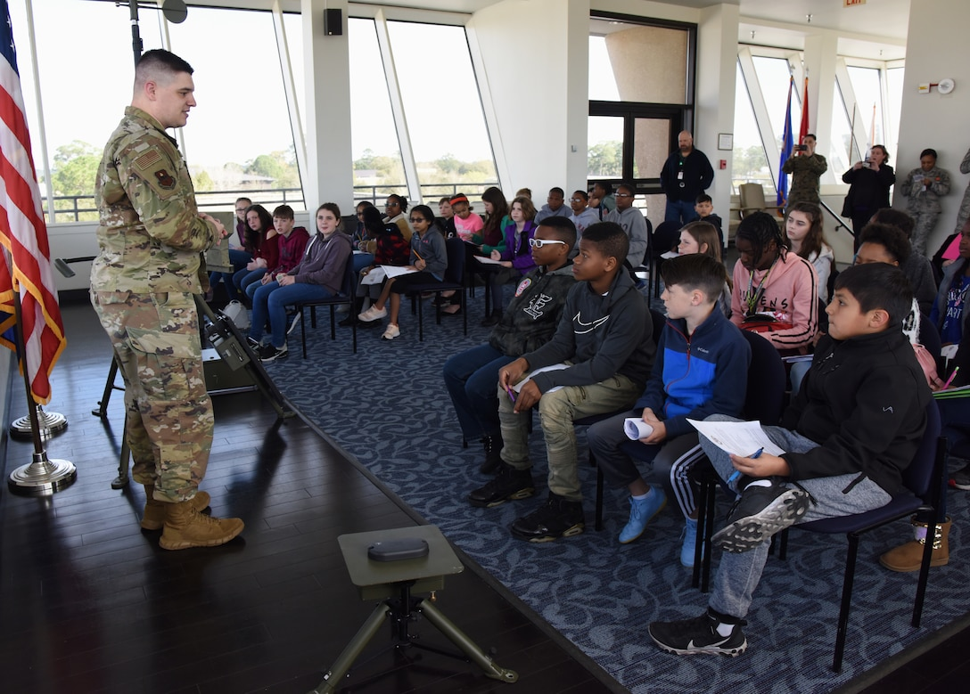 U.S. Air Force Staff Sgt. Christopher Spears, 335th Training Squadron instructor, provides a weather training briefing to school-aged children during Biloxi School District Career Exploration Day on Keesler Air Force Base, Mississippi, March 7, 2019. The children also toured the Keesler Fire Department, 334th TRS air traffic control school and received a demonstration from the 81st Security Forces Squadron military working dogs. (U.S. Air Force photo by Kemberly Groue)
