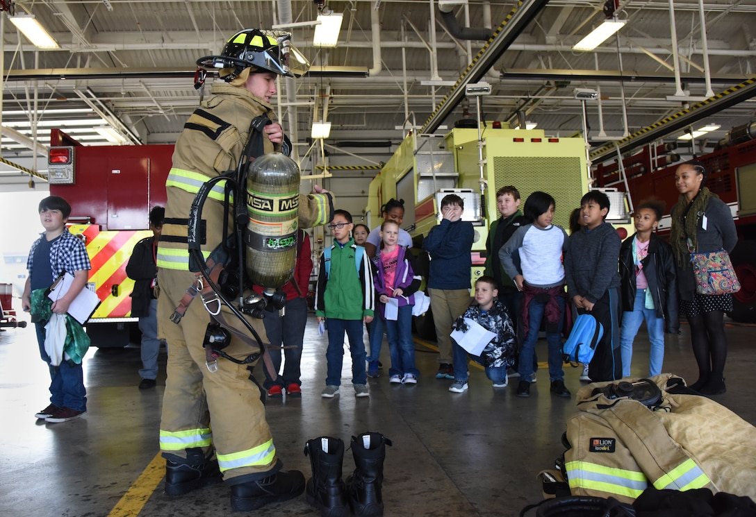 Seth Corn, 81st Infrastructure Division driver operator, demonstrates to school-aged children how to quickly get dressed in firefighter gear during Biloxi School District Career Exploration Day on Keesler Air Force Base, Mississippi, March 7, 2019. The children also toured the 334th Training Squadron air traffic control school, 335th TRS weather facility and received a demonstration from the 81st Security Forces Squadron military working dogs. (U.S. Air Force photo by Kemberly Groue)
