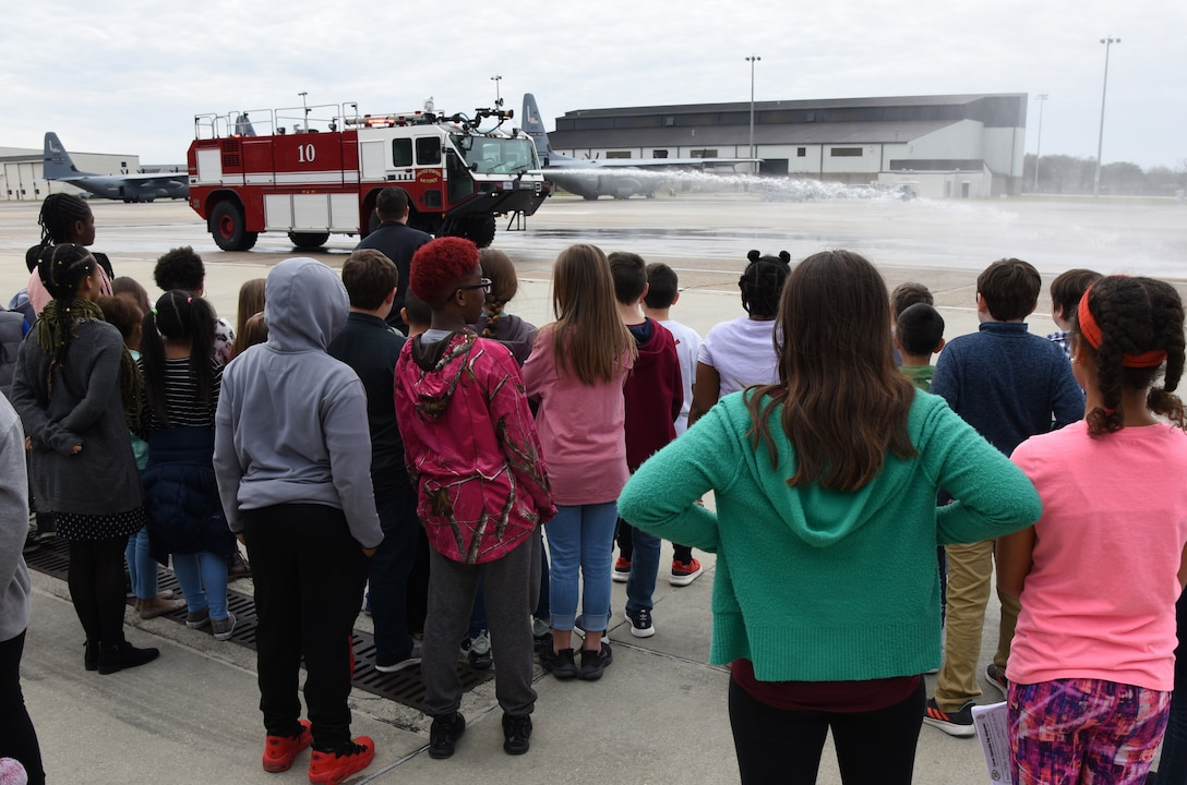 Members of the Keesler Fire Department spray water from a fire truck for school-aged children during Biloxi School District Career Exploration Day on Keesler Air Force Base, Mississippi, March 7, 2019. The children also toured the 334th Training Squadron air traffic control school, 335th TRS weather facility and received a demonstration from the 81st Security Forces Squadron military working dogs. (U.S. Air Force photo by Kemberly Groue)