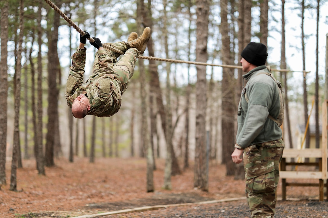 A service member pulls himself along a rope.