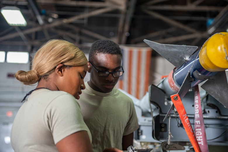 U.S. Air Force Senior Airman Genesa Williams, 20th Maintenance Group Operations weapons standardization load crew member team lead, trains a new Airman on how to attach a missile during Women's History Month at Shaw Air Force Base, S.C., March 8, 2019.