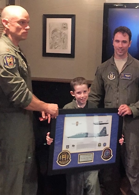 Maj. Elliott Nelsen (left) and Lt. Col. Jeremy Downs, 97th Flying Training Squadron, Sheppard Air Force Base, Texas, pose with Connor, a young cancer patient who had the one-in-a-lifetime opportunity to be an aircraft commander for a day thanks to Downs and Nelsen. When they learned about Connor's illness and his desire to be a pilot, the 97th FTS instructor pilots worked with teammates across the 80th Flying Training Wing to make sure Connor had a day he would never forget. (Courtesy photo)