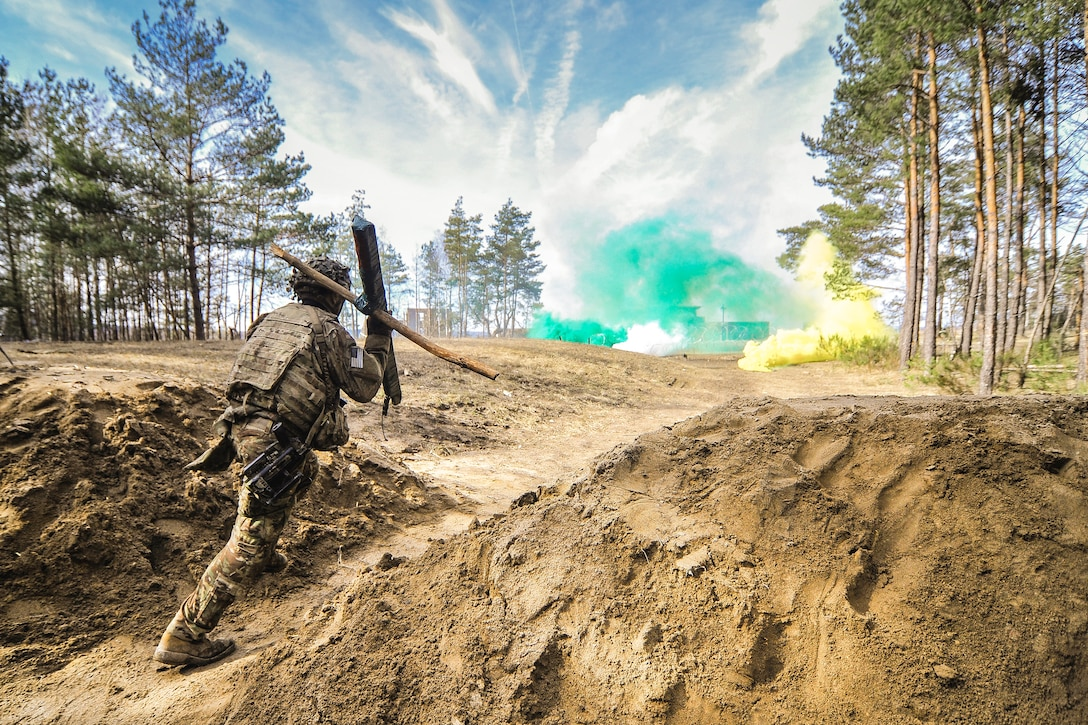 A soldier holding two pieces of wood walks in between two dirt mounds towards green and yellow smoke in the distance