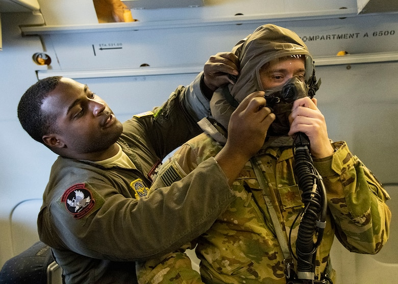 Senior Airman Dorian Cozart, boom operator with the 2nd Air Refueling Squadron, assists Major Brett Kubat, KC-10 Extender pilot with the 2nd ARS, in donning his Aircrew/Eye Respiratory Protection (AERP) gear prior to takeoff March 7, 2019, during Exercise Jersey Devil 19 in Gulfport, Miss. Jersey Devil was aimed at preparing Airmen to respond to complex threats anywhere, anytime. (U.S. Air Force photo by Airman 1st Class Zoe M. Wockenfuss)