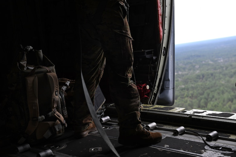 Feet and lower legs are shown beside a backpack and an open door on a C-130J.