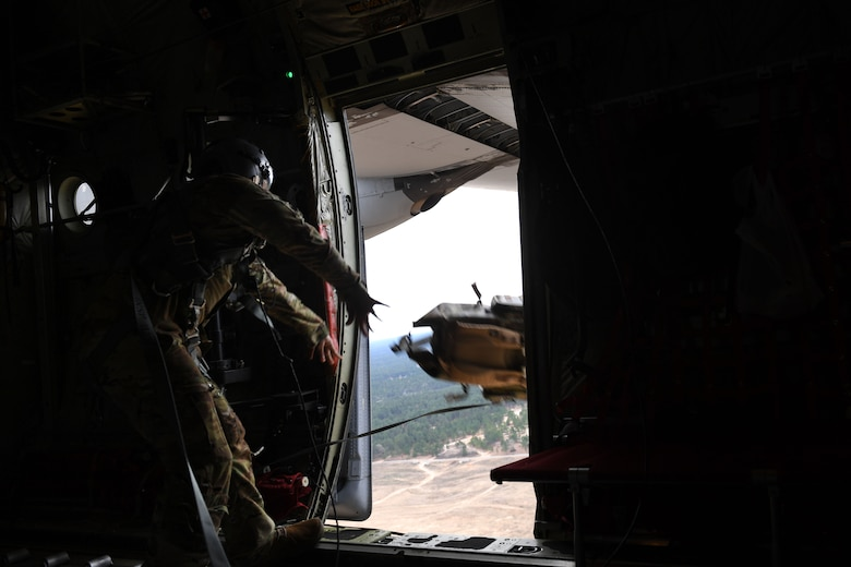 An Airman throws a backpack out of a C-130J, while in the air.