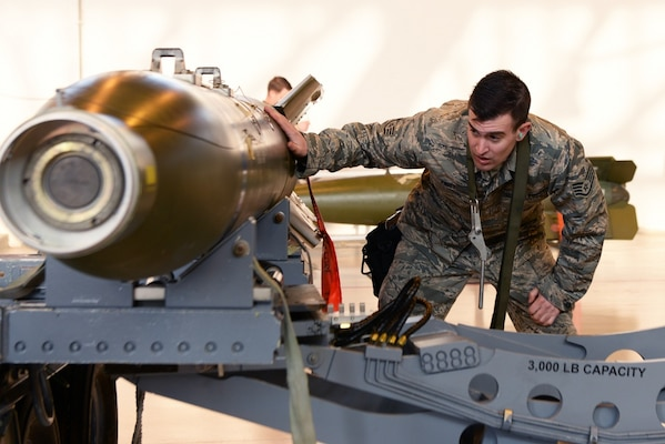 U.S. Air Force Staff Sgt. Ryan Pritt, 31st Aircraft Maintenance Squadron weapons load crew chief, oversees the lifting of a training GBU-10 J/B bomb at Aviano Air Base, Italy, Feb. 19, 2019. The weapons load crew members load a computer control group onto the armament after attaching it to a F-16 Fighting Falcon.