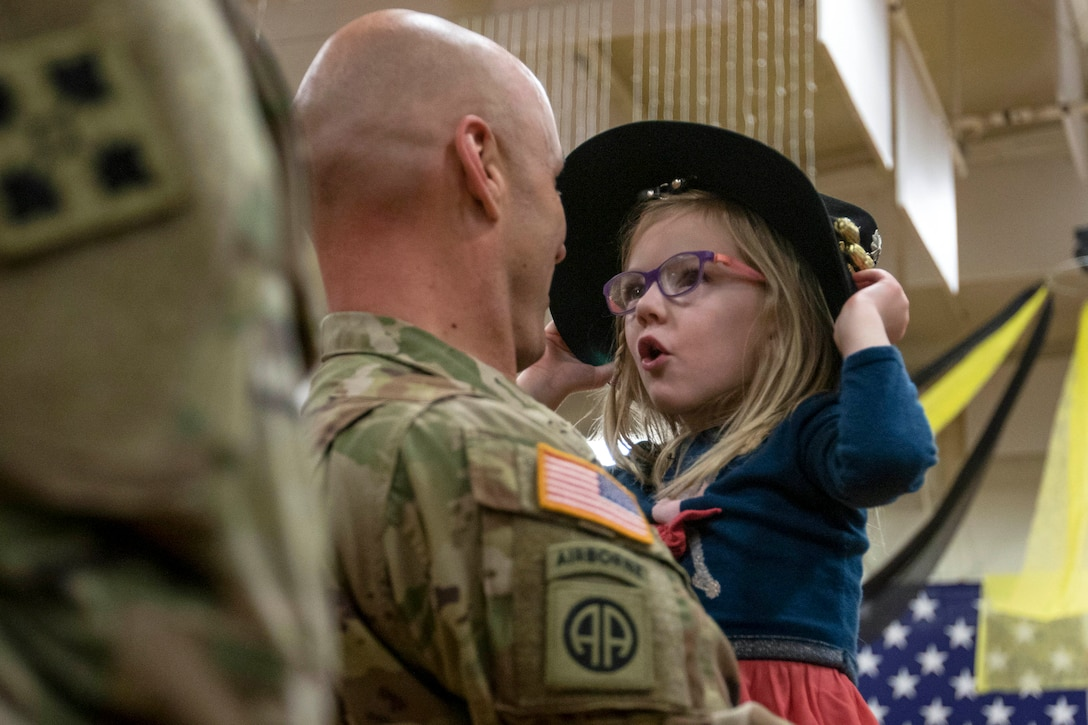 A soldier holds a girl, who is trying on his hat and talking to him.