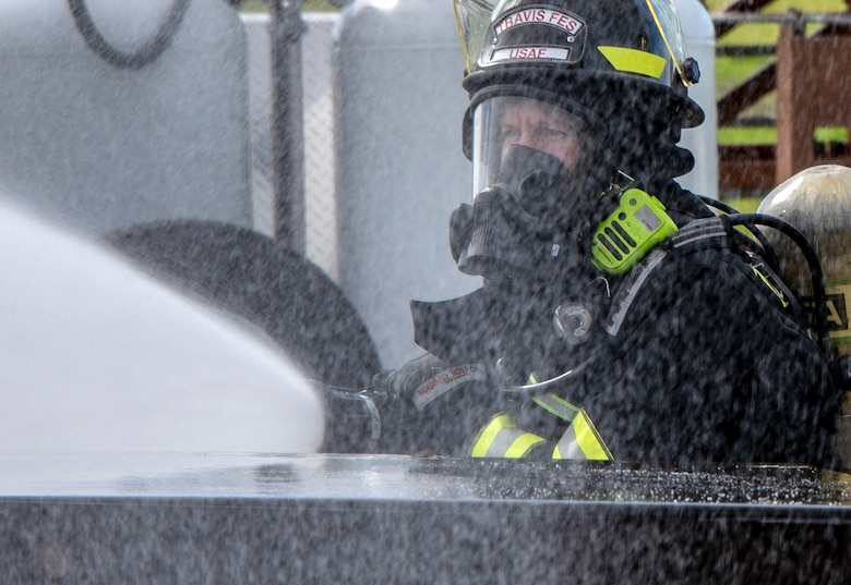 U.S. Air Force Airman 1st Class Autum Boomershine a firefighter for the 60th Civil Engineer Squadron, sprays water on a simulated crash site during a major accident response exercise, Feb. 28, 2019, Travis Air Force Base, California. The MARE was used to evaluate how different base agencies respond to emergency situations. (U.S. Air Force photo by Heide Couch)