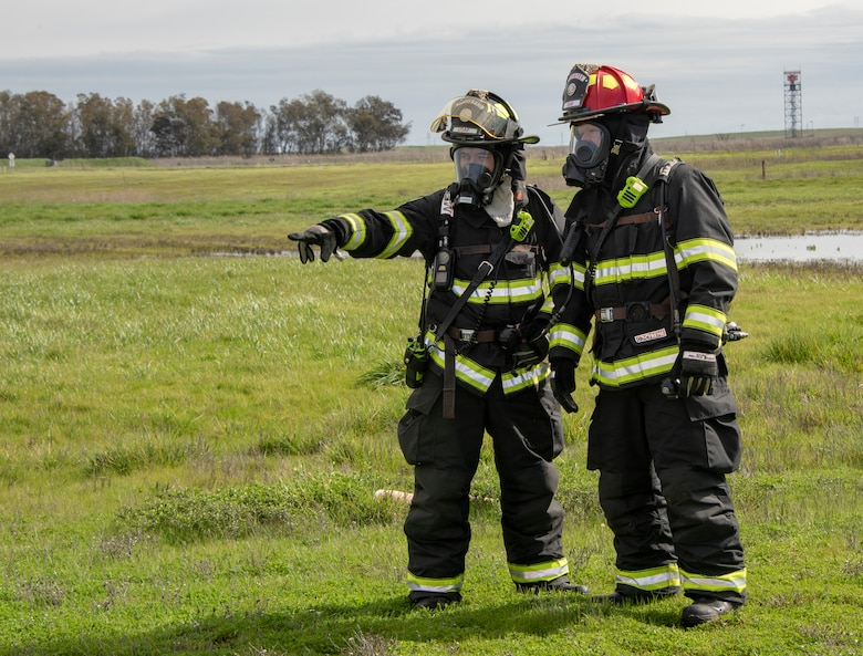 U.S. Air Force Tech. Sgt. Keenan Grimmer and Staff Sgt. Michael Hoh, firefighters with the 60th Civil Engineer Squadron, survey the debris field at a simulated crash site during a major accident response exercise, Feb. 28, 2019, Travis Air Force Base, California. The MARE was used to evaluate how different base agencies respond to emergency situations. (U.S. Air Force photo by Heide Couch)
