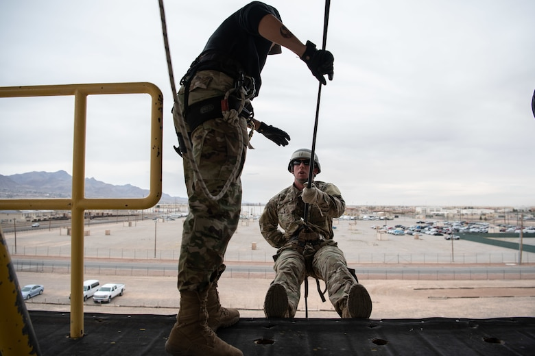 U.S. Army Cpl. Alexandra Perez, Iron Training Detachment air assault instructor, instructs Staff Sgt. James Tienor, 377th Security Forces Group Air Assault trainee, on proper rappelling techniques at Fort Bliss, TEXAS., March 8, 2019. Nine members of the 377th SFG at Kirtland Air Force Base N.M., graduated from the Fort Bliss Air Assault Training School March 11. (U.S. Air Force photo by Staff Sgt. J.D. Strong II)