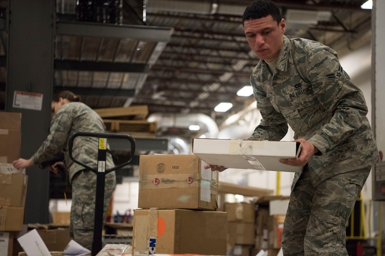 Alaska Air National Guardsmen Airman 1st Class Alan Merritt and Airman 1st Class Lauren Scanlan, both 176th Logistics Readiness Squadron ground transportation personnel, prepare a shipment of items for delivery, March 11, 2019, at Joint Base Elmendorf-Richardson, Alaska. In one of the newest total force integration associations of its kind, the 673d Logistics Readiness Squadron Materiel Management flight is conducting a complete C-17 aircraft supply turnover to the 176th LRS.