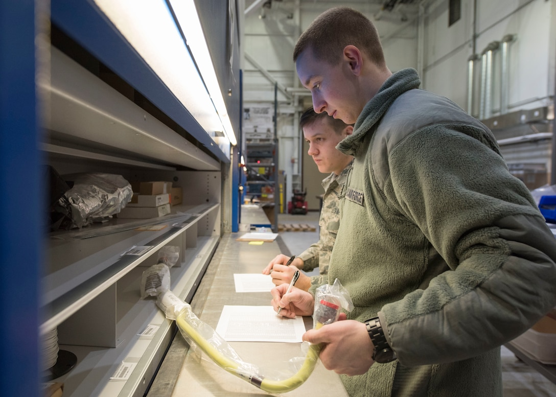 New Hampshire Air National Guardsmen Airman 1st Class Ryan Allen and Airman Timothy Gregoire, both from the 157th Logistics Readiness Squadron's central storage, validate the specific location and stock numbers of parts, March 11, 2019, at Joint Base Elmendorf-Richardson, Alaska. While at JBER, the Guardsmen are training as well as helping with the transfer of all C-17 Globemaster III supply turnover from the 673d LRS to the Alaska Air National Guard's 176th LRS.