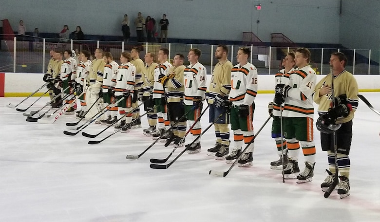 Members of the Miami Hurricanes hockey team stand in unity with the Air Force Technical Applications Center hockey club during the National Anthem Feb. 23, 2019 at an exhibition game at Pembroke Pines Ice Arena, Miami's home rink.  AFTAC went on to defeat the 'Canes 12-8.  (Courtesy Photo)