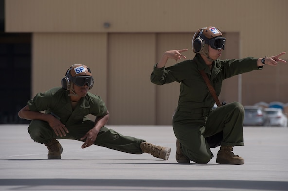 "U.S. Navy Airman Shannon Barde, left, Electronic Attack Squadron 135 (VAQ-135) ""Black Ravens"" plane captain, and U.S. Navy Airman Waisum Cheung, VAQ-135, use hand signals to ensure pre-flight inspections for an EA-18G Growler are conducted safely March 4, 2019, at Al Udeid Air Base, Qatar. VAQ-135 is deployed to the U.S. 5th Fleet area of operations in support of naval operations to ensure maritime stability and security in the Central Region, connecting the Mediterranean and the Pacific through the western Indian Ocean and three strategic choke points. The squadron's EA-18G Growlers employ an electronic attack capability in support of combat missions across the region. (U.S. Air Force photo by Tech. Sgt. Christopher Hubenthal)"