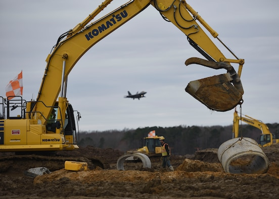Aspen Construction workers move a segment of cement pipe on the airfield construction site at Joint Base Langley-Eustis, Virginia, March 4, 2019.