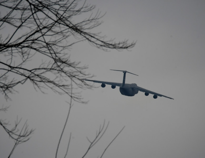 """A C-5 aircraft makes a banking turn of approximately 15 degrees as it lifts off from training with the 932nd Airlift Wing March 2, 2019 at Scott Air Force Base, Illinois.  The 932nd Aeromedical Evacuation Squadron took part in a C-5M Super Galaxy patient evacuation training with the 142nd Aeromedical Evacuation Squadron, visiting from New Castle Air National Guard Base, Delaware, at Scott AFB, Illinois, March 2.  The training consisted of setting up litters on the back of seats and in the cargo hold. Only three AES's have been certified in the C-5 patient evacuation training. C-5 training prepares units who are uncertified to do aeromedical evacuations and to be one step closer to completing the training.   """"Our prime aircrafts are C-130, KC-135 and C-17,"""" said Senior Master Sgt. Tonya Hupp, 932nd AES Operations Superintendent. """"The C-5 is our opportune aircraft that we can move patients in the event that we are needed, if there were a mass casualty.""""  (U.S. Air Force photo by Lt. Col. Stan Paregien)"""