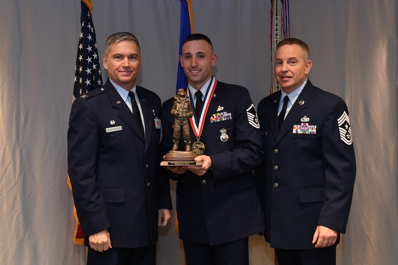 Master Sgt. Michael Wenger, flight chief with the 911th Security Forces Squadron, is awarded 911th Airlift Wing Senior Noncommissioned Officer of the Year by Col. Douglas N. Strawbridge, commander of the 911th AW, and Chief Master Sgt. Christopher D. Neitzel, command chief of the 911th AW, during the 911th AW Annual Award Ceremony at the Pittsburgh International Airport Air Reserve Station, Pennsylvania, March 2, 2019. The 2018 awards ceremony recognized Airmen who went above and beyond in their service for the year 2018. (U.S. Air Force photo by Senior Airman Grace Thomson)