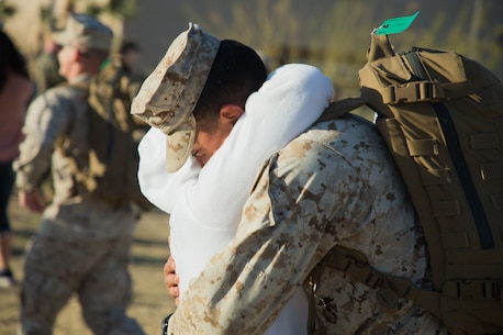 A Marine with 3rd Battalion, 4th Marines, 7th Marine Regiment, 1st Marine Division, hugs his mother during a homecoming ceremony at Victory Field on Marine Corps Air Ground Combat Center (MCAGCC), Twentynine Palms, Calif., March 8, 2019. The Marines and sailors returned from a six-month deployment to Kuwait. (U.S. Marine Corps photo by Pfc. Shane T. Beaubien)
