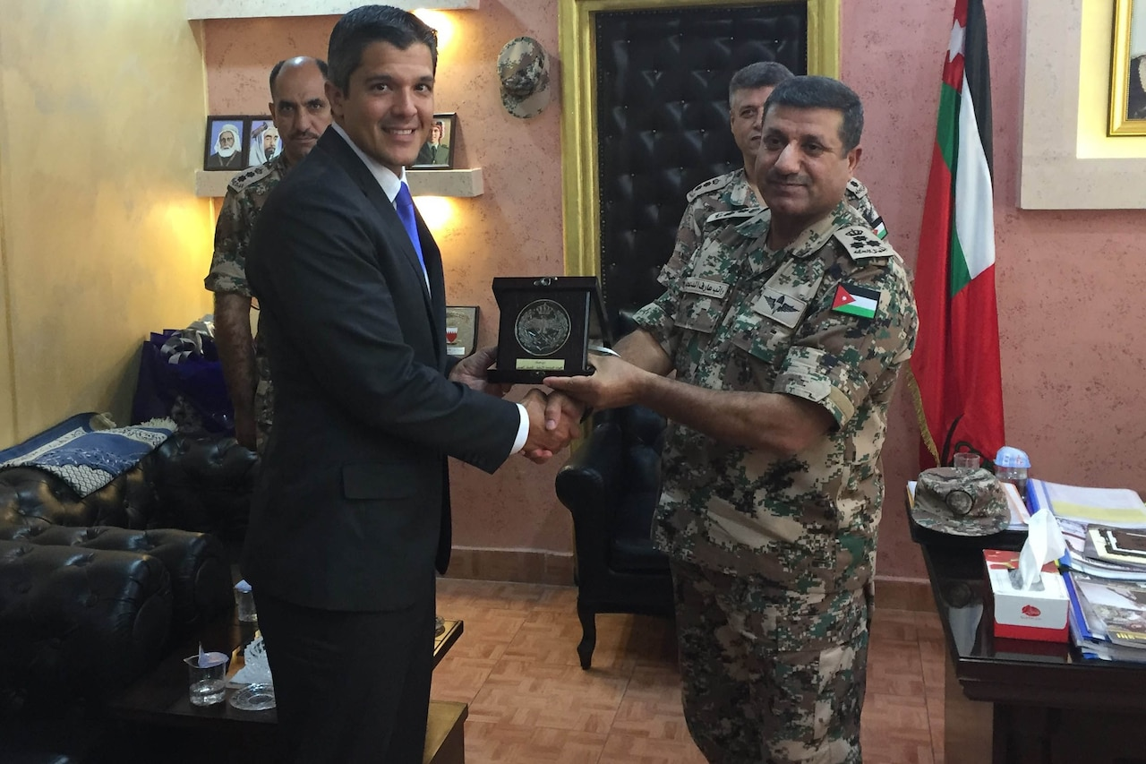 A man shakes hands with a Jordanian military officer while two others stand in the background.
