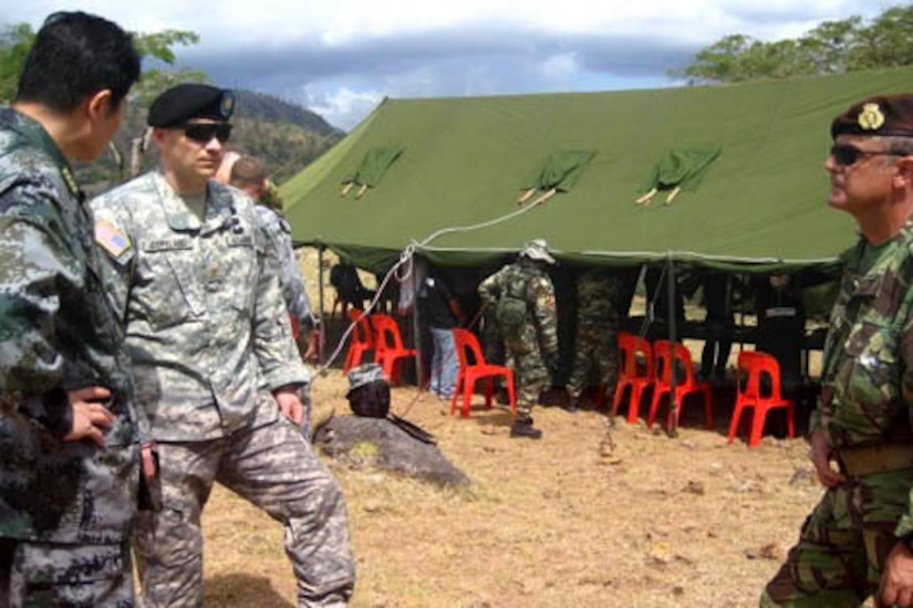 Army Lt. Col. Rex Copeland stands talking to two foreign military colonels near a tent.