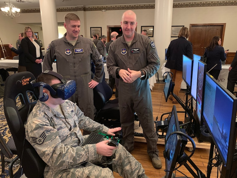 Lt. Col. Joe Stallings (left), 12th Flying Training Wing Innovation Director, and Capt. Calogero San Filippo (right), Pilot Training Next instructor pilot, discuss virtual-reality flying technology while Staff Sgt. Joseph Sabin, Air Education and Training Command, flies a VR sortie at the PTN Technology Expo at Joint Base San Antonio-Randolph, Texas, March 12, 2019.  Flying training wings will formally begin integrating innovations from PTN into the undergraduate pilot training curriculum beginning May 31, 2019.