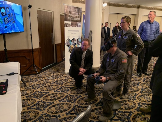 Col. Samantha Weeks (right), 14th Flying Training Wing commander, and Maj. Ryan Brewer (seated), 14th FTW SparkCell director, sample emergency procedures augmented-reality technology at the PTN Technology Expo at Joint Base San Antonio-Randolph, Texas, March 12, 2019.  Flying training wings will formally begin integrating innovations from PTN into the undergraduate pilot training curriculum beginning May 31, 2019.
