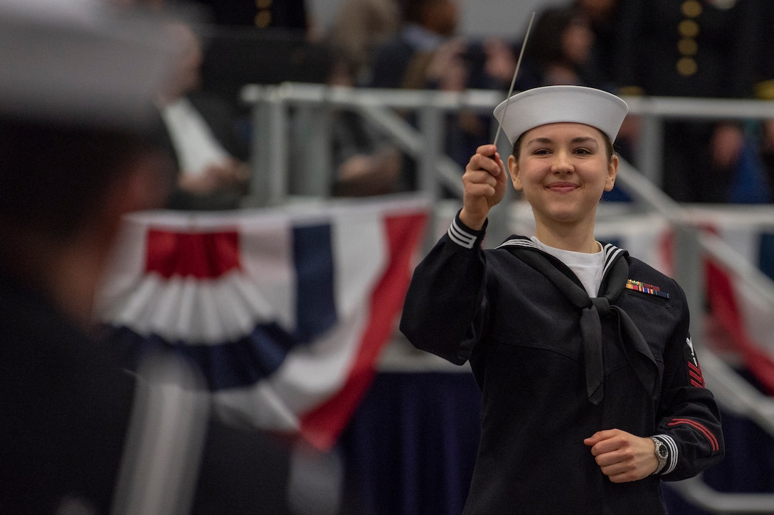 A female service member waves a baton during a ceremony.