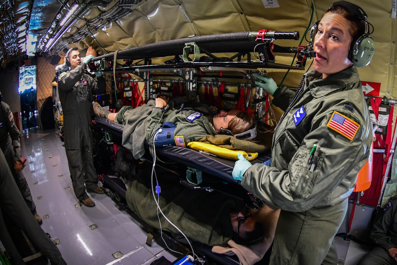 Air Force service members tend to a patient aboard an Air Force plane.