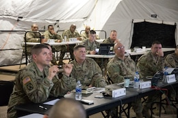 """Maj. Gen. Flem B. """"Donnie"""" Walker Jr., commanding general, 1st Theater Sustainment Command, along with his staff, listen to a brief Feb. 18, during the unit's Early Entry Command Post (EECP) exercise at Fort Campbell, Ky. When Walker took command of the unit almost two years ago, he directed his staff to substantially increase the unit's expeditionary capabilities.  (U.S. Army photo by Master Sgt. Jonathan Wiley)"""