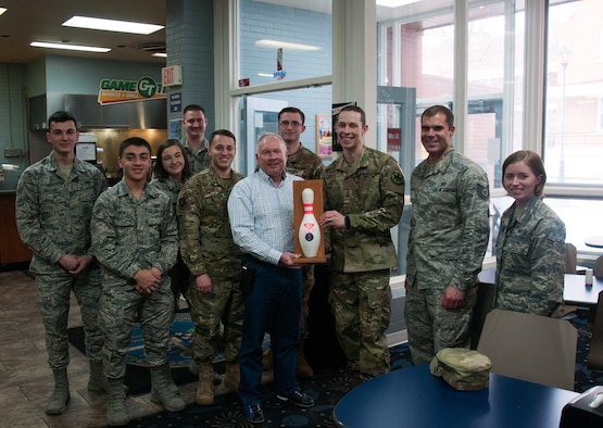 Maj. Gen. Fred Stoss, 20th Air Force commander, and members of the 90th Missile Wing finance flight hold the 20th Air Force Bowling Tournament trophy at F. E. Warren bowling alley on F. E. Warren AFB Wyo., March 8, 2019. 20th Air Force headquarters staff organized a bowling tournament in honor of the 75th anniversary of 20th Air Force. (U.S. Air Force photo by 1st Lt Ieva Bytautaite)