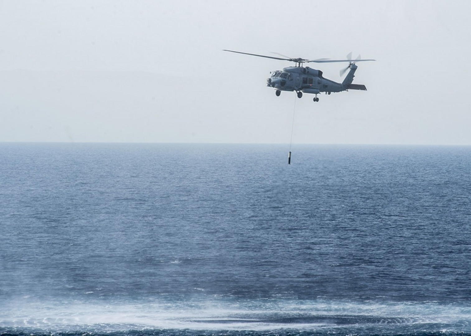 An MH-60 Seahawk helicopter assigned to the Grandmasters of Helicopter Maritime Strike Squadron (HSM) 46 deploys a sonobuoy, a tactical sonar system used for tracking submarine activity.