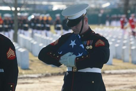 A Marine Body Bearer, Bravo Company, Marine Barracks Washington D.C., holds the National Flag during a full honors funeral for Lt. Gen. Leo Dulacki at Arlington National Cemetery, Arlington, Virginia, March 13, 2019.