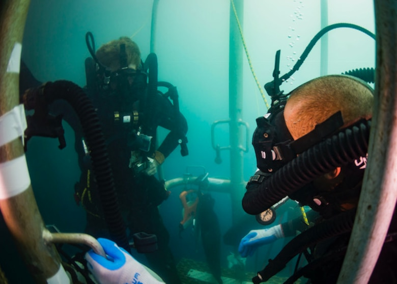 U.S. Navy Divers assigned to Mobile Diving and Salvage Company ONE-EIGHT embarked aboard USNS Salvor (T-ARS 52), wait on a diving stage during a two-hour decompression stop after diving to 240 feet off the coast of Madang, Papua New Guinea, Dec. 7, 2018.